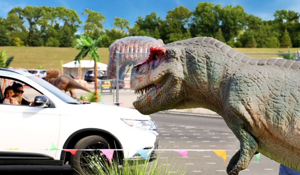 A car driving by a dinosaur statue