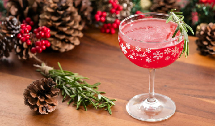 A festive Christmas cocktail, surrounded by pine combs