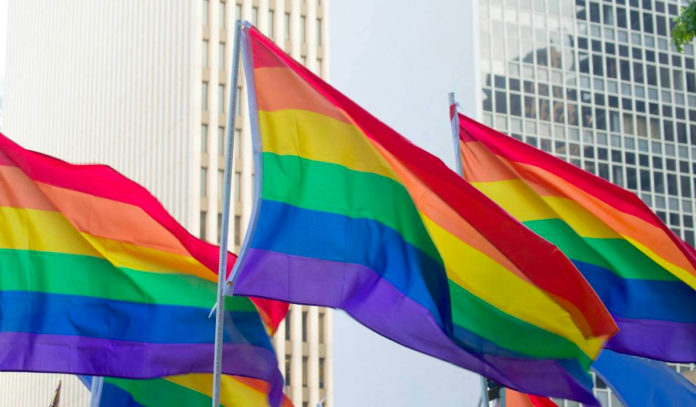 Three Pride flags wave in front of Downtown skyscrapers.